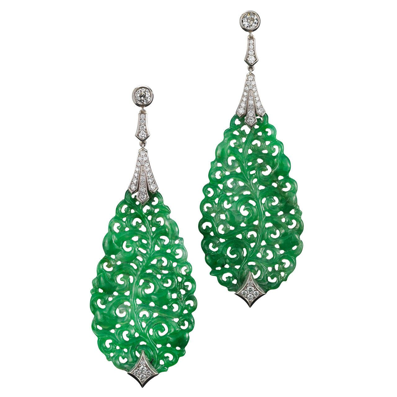 Fred Leighton Carved Jade and Diamond Foliate Pendant Earrings. Pierced floral motif jadeite drops are accented with a total of approximately 1.14 carats of round diamonds mounted in 18 karat white gold. The jade plaques measure approximately 48 by 25 millimeters and the earring measures approximately 3 inches in length.