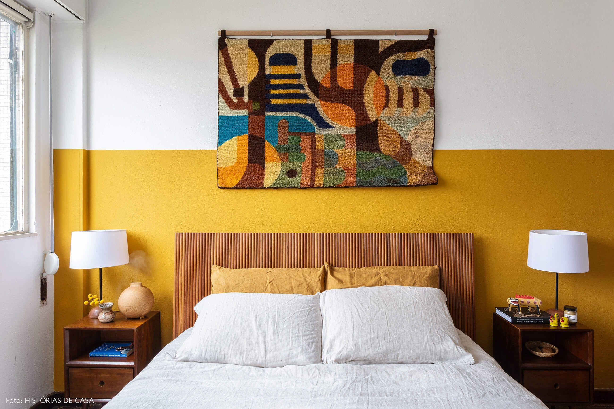 dcd7cf4cc7 Quarto de casal com cama de madeira e parede mostarda tem tapeçaria  pendurada e criado-mudo vintage.