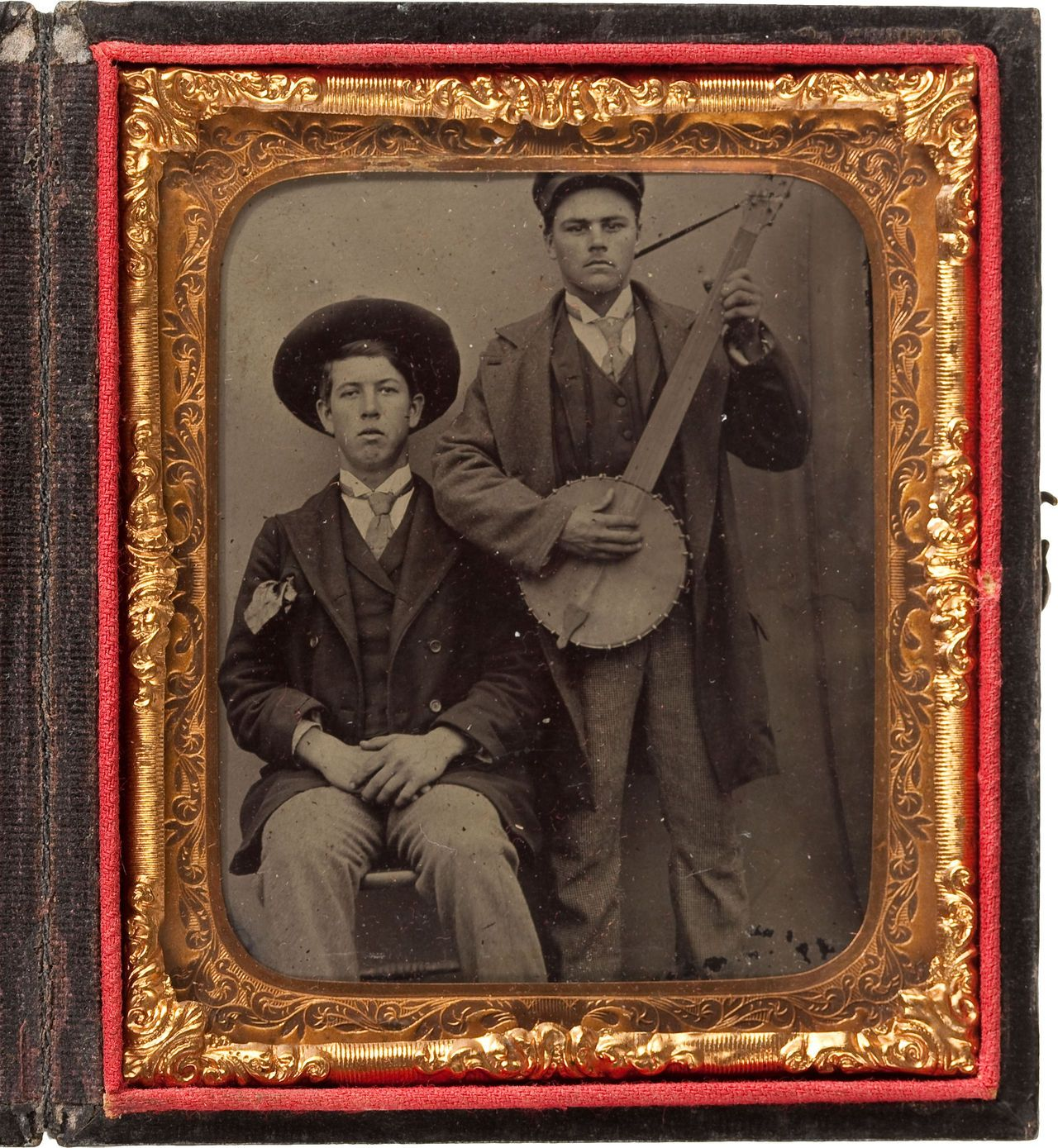 ca. 1860's, [Tintype portrait of two young men; one with a wide brimmed hat and large handkerchief, the other playing a five string ba...
