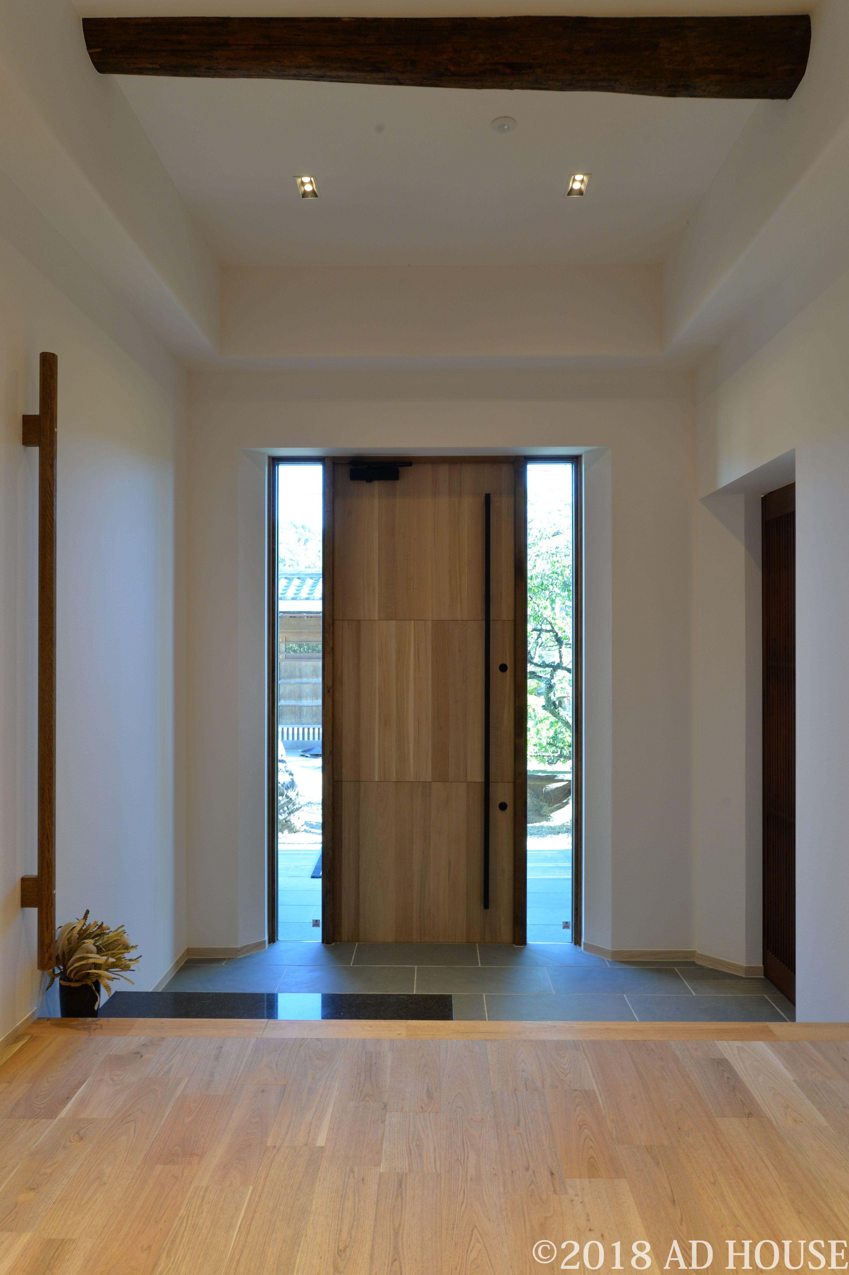オーク材の断熱玄関扉で 両側はめ殺しの窓から光を取り込んでいる