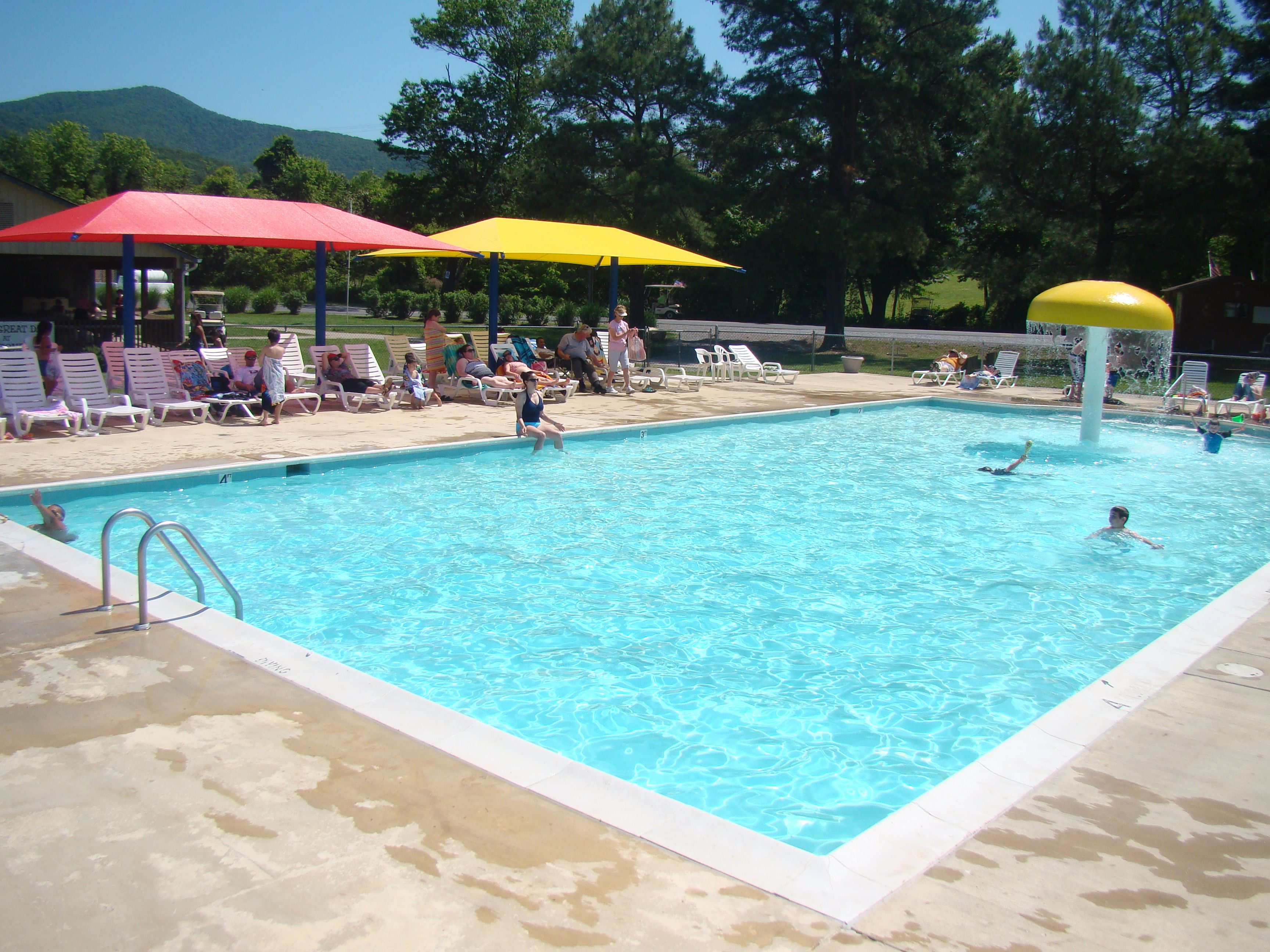 One Of Our Pools With The New Shade Umbrellas Come Hang In The Shade With Yogi Bear Boo Boo And Cindy Bear Shade Umbrellas Yogi Bear Jellystone Park