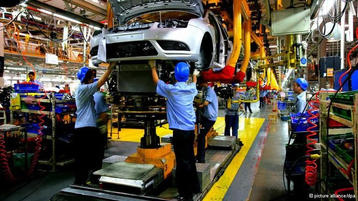 Chinese factory workers assemble Ford cars on the production line - auto mechanic job description