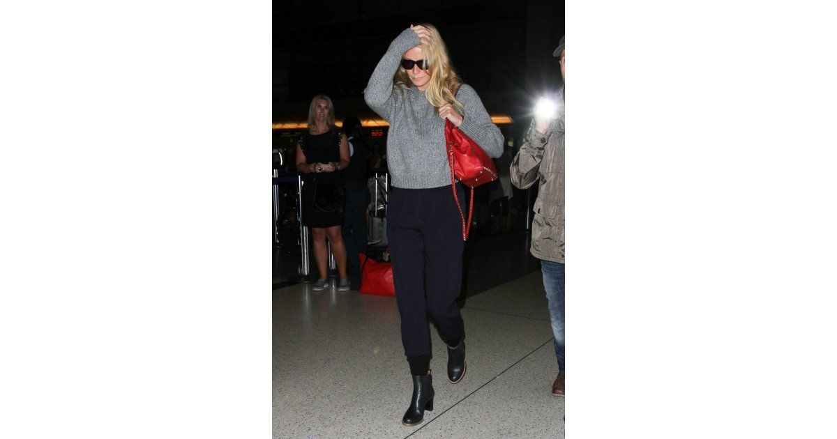 Gwyneth Paltrow made a case for cool and casual in a cozy gray sweater, black pants, and a pop of red on her bag while making her way from the jetway.