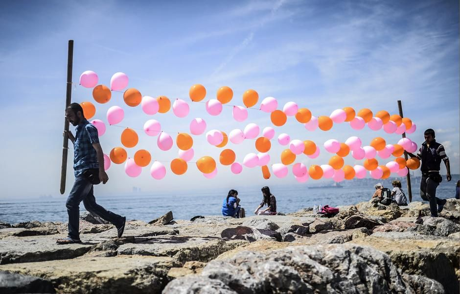 Men carry balloons near the sea at Kadikoy on May 3, 2014, in Istanbul. (Photo: Bulent Kilic-AFP)