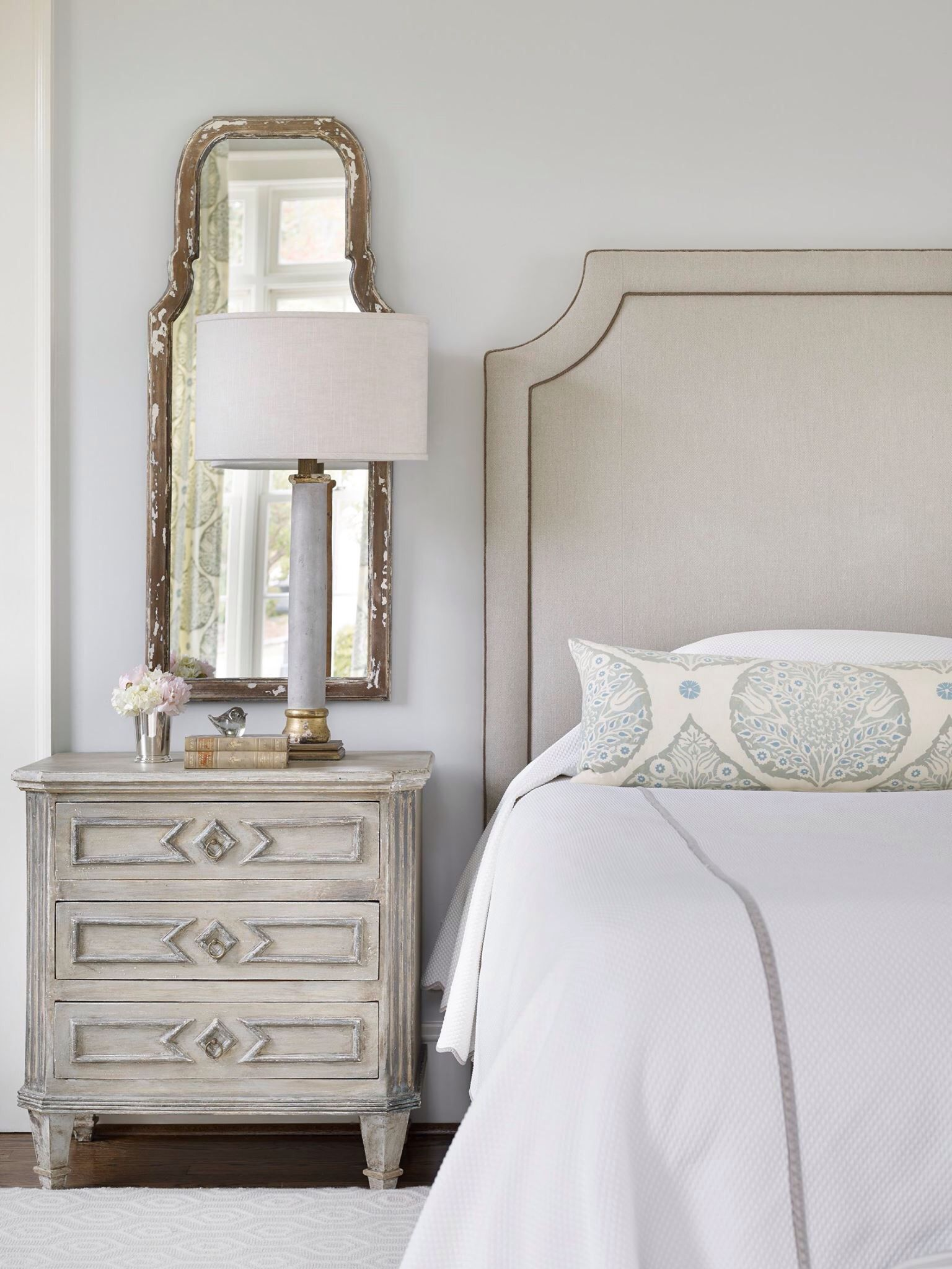 Traditional master bedroom boasts a gray headboard on bed with white and  gray bedding and a gray leaf print lumbar pillow next to a gray nightstand  and an ...