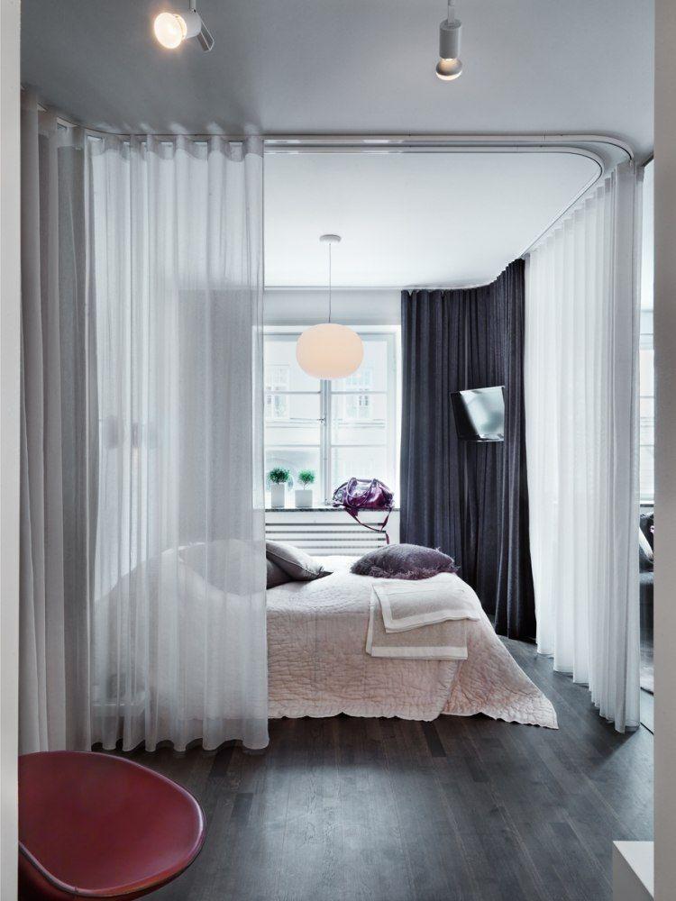 Bett mit schieren Gardinen umgeben oder mit dichten Vorhängen