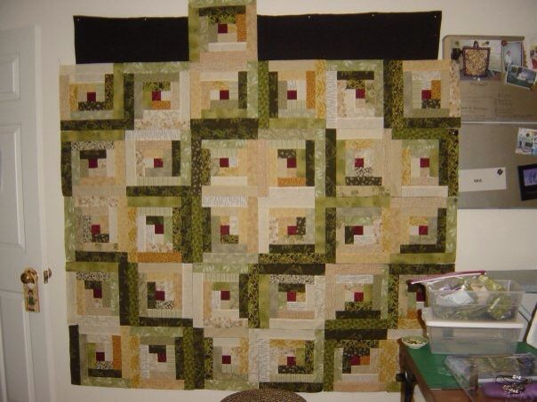 Log cabin blocks in contrasting green & gold asian fabrics are set in a barnraising layout to give this classic quilt design a modern flavor. Now... if I could just finish this UFO!