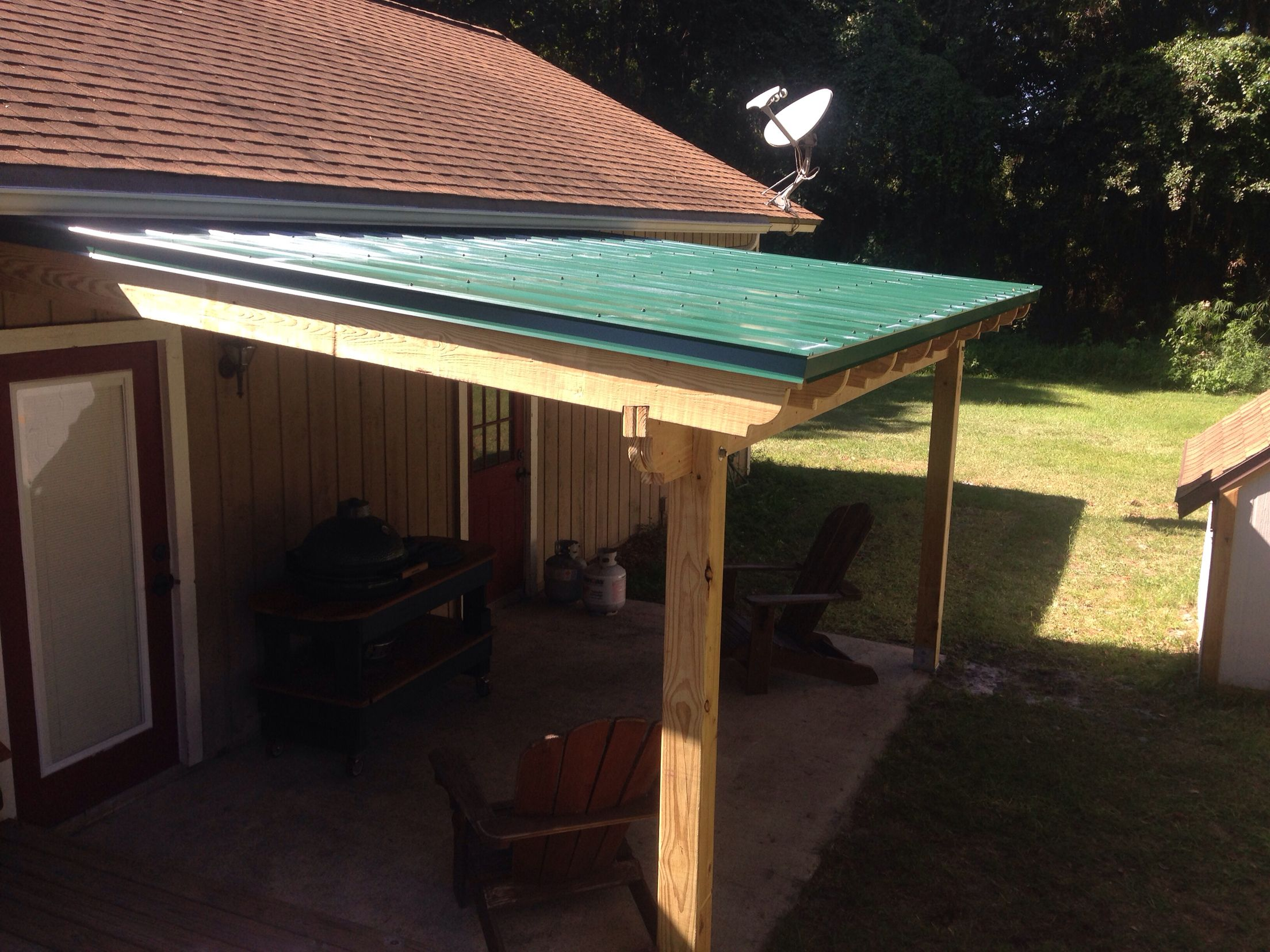 Patio roof with Hunter green metal roofing covered deck covered