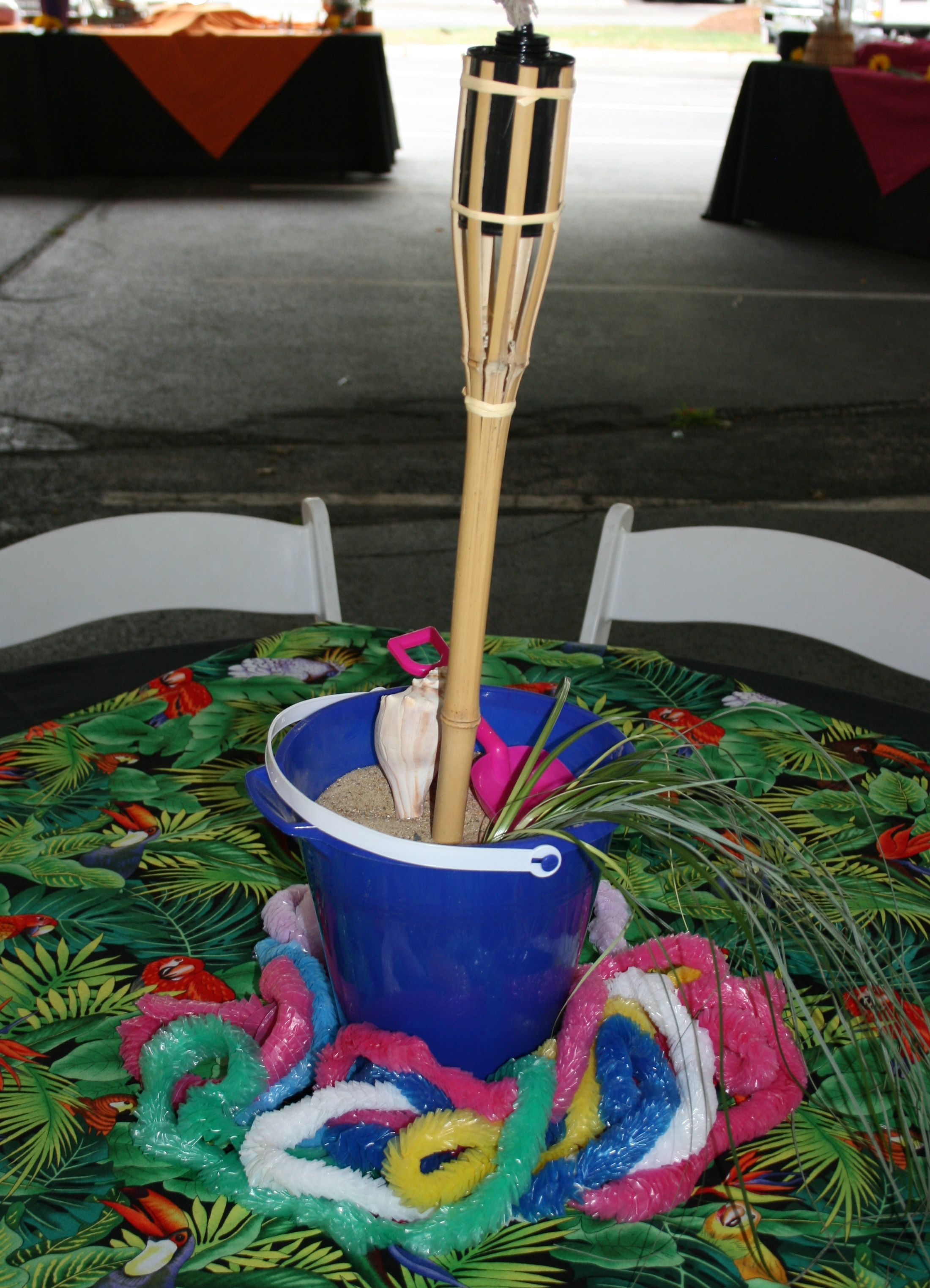 Beach bucket centerpiece with mini tiki torch used at a