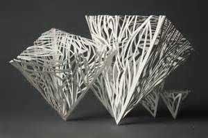This art piece shows a series of geometric shapes that were carve out of paper and stuck together to form the 3-D shapes you see here.