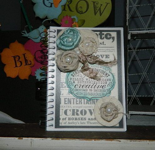 Altered notebook featuring ribbon flowers. Video tutorial on flowers on the link after 1/15/13.   Happy Crafting!~ Dee
