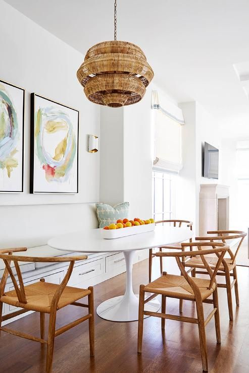 Clean Breakfast Nook Is Filled With A 3 Tier Woven Basket Chandelier  Illuminating An Oval Saarinen Dining Table Lined With 4 Hans Wegner  Wishbone Chairs As ...