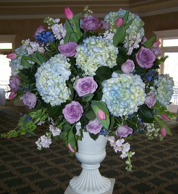 Large arrangement featuring blue hydrangeas lavender