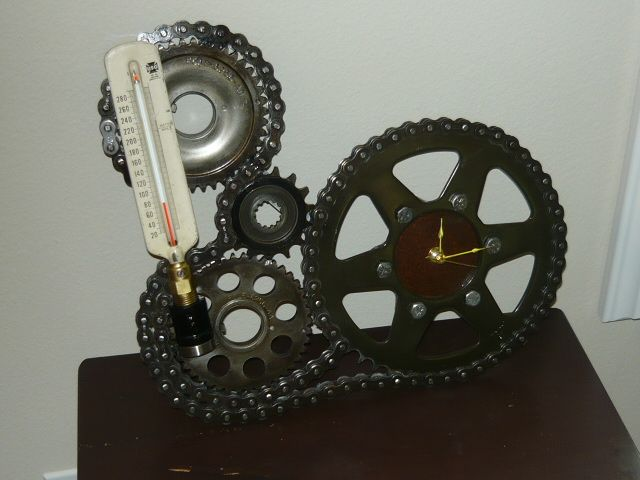Wall clock made from used motorcycle and car parts. Utilizes a ...