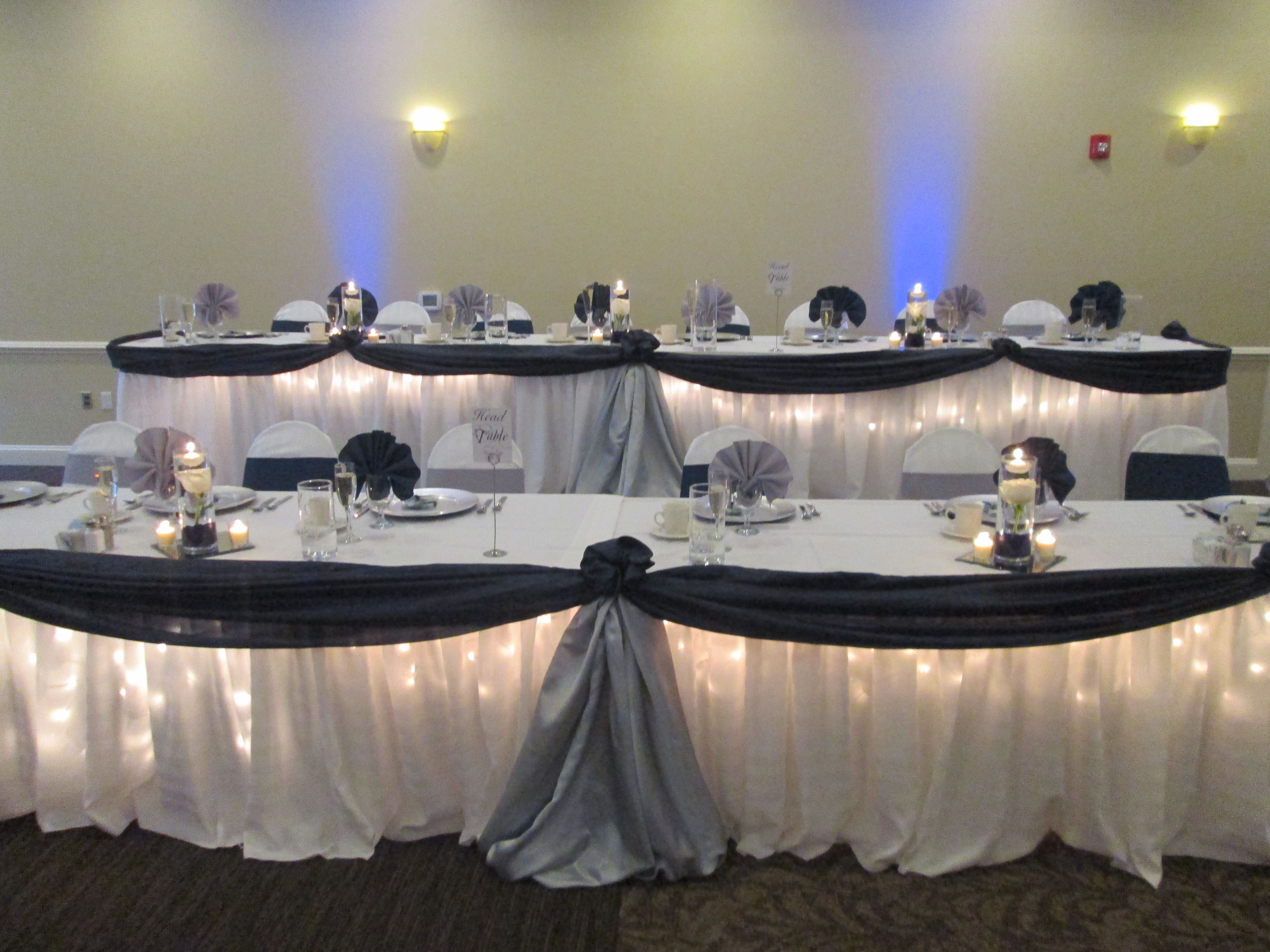 long table setup wedding reception%0A Navy and Silver swag with lighting underneath head table set up    caprottiscatering  capriottispalazzo