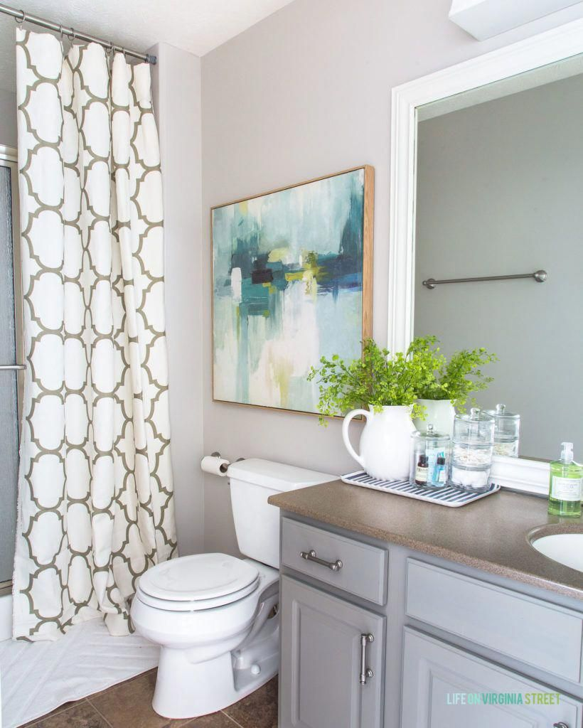 Gorgeous Coastal Inspired Bathroom With Green Blue Art A Tan And White Shower Curtain And G Tan Bathroom Decor Coastal Inspired Bathrooms Bathroom Makeover