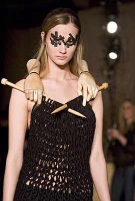 Combines a studio art necklace with a fetching knit sheath. A twofer. Three, if you count the electrician's-tape mascara.