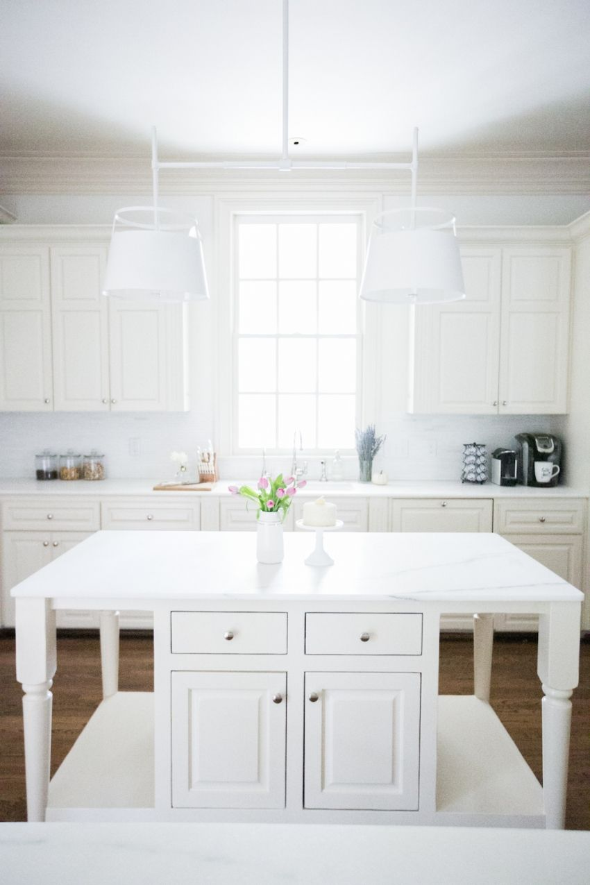 Kitchen window over sink  gorgeous white marble island with light fixture by urban electric