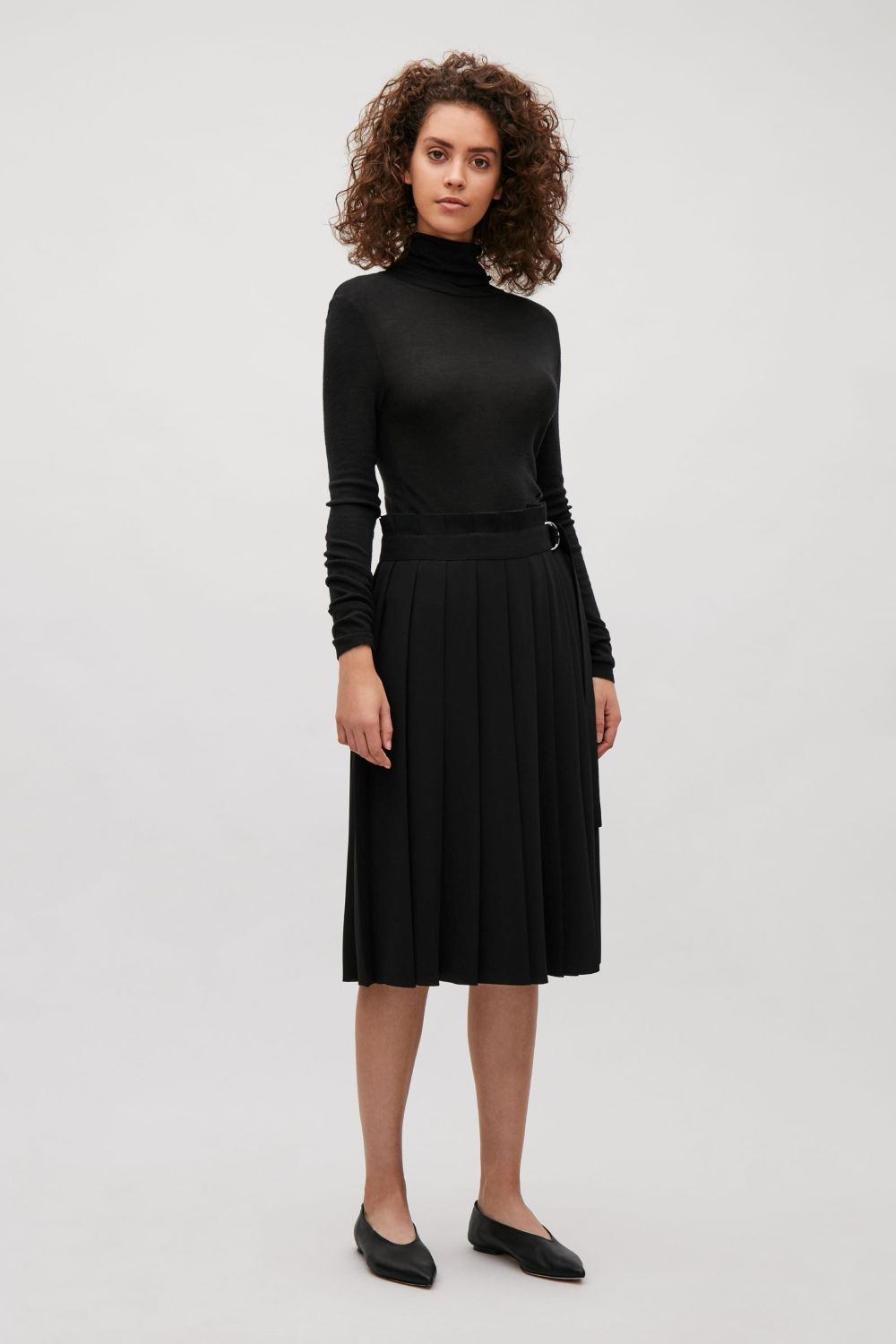 A wrap-over style, this skirt is made from a crepe material with deep pleats. Designed with a D-ring fabric belt, it has two inside buttons for an adjustable waist, a simple, straight hemline and laser cut finishes.