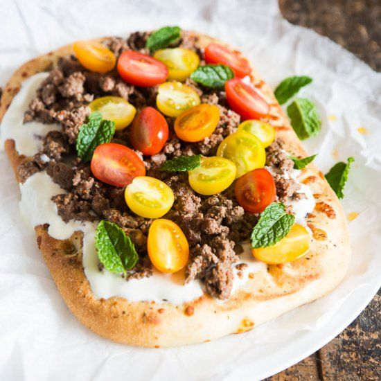 Spicy flatbread topped with yoghurt, minced meat with spices and herbs and fresh cherry tomatoes