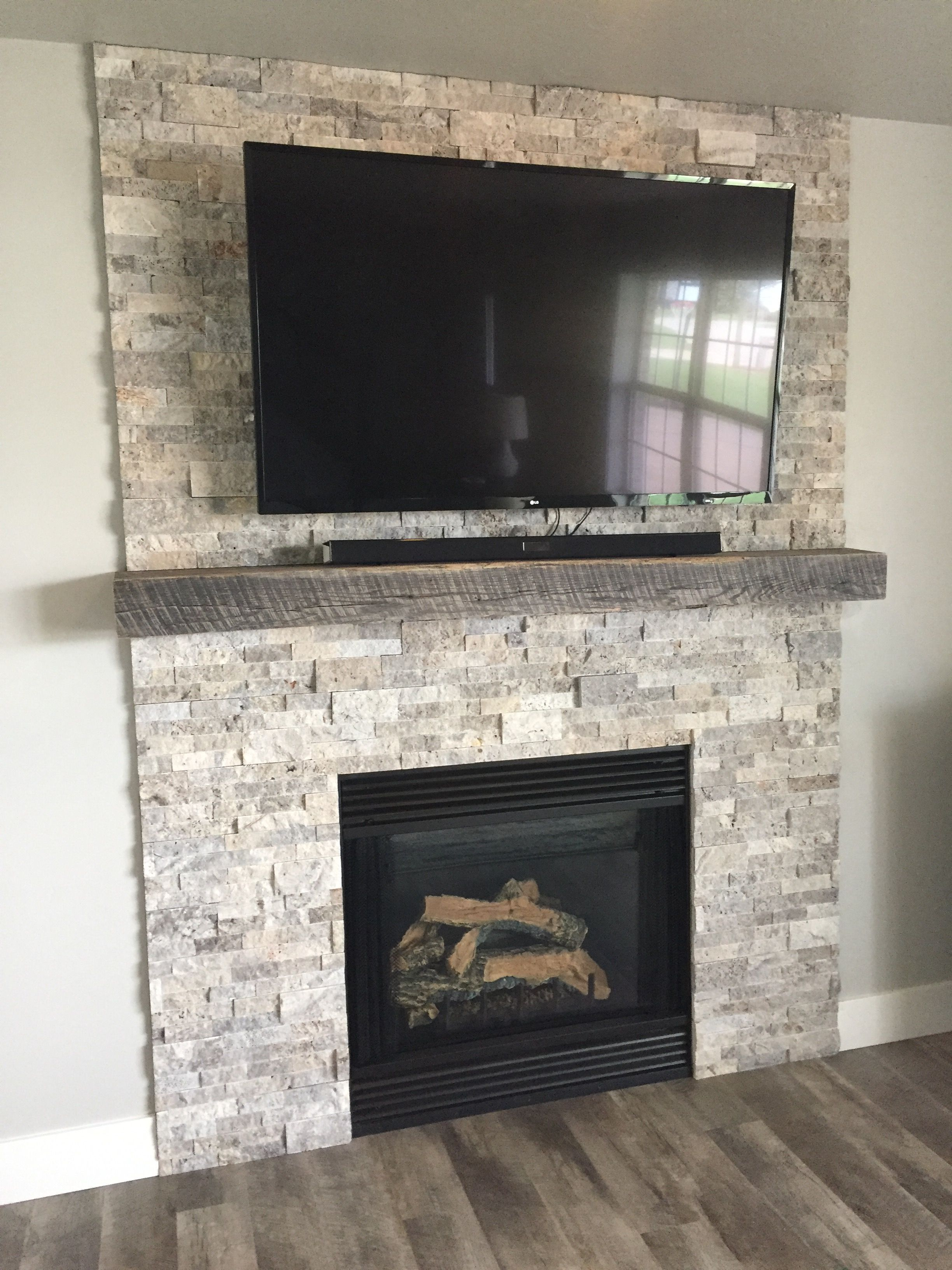 Silver travertine stacked stone and a reclaimed jim beam mantel for