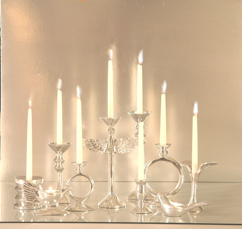 Polished silver candle stands by Nima Oberoi Lunares. Add a bit of glamour and soul to your home with these stunning O and angel wing candle holders.