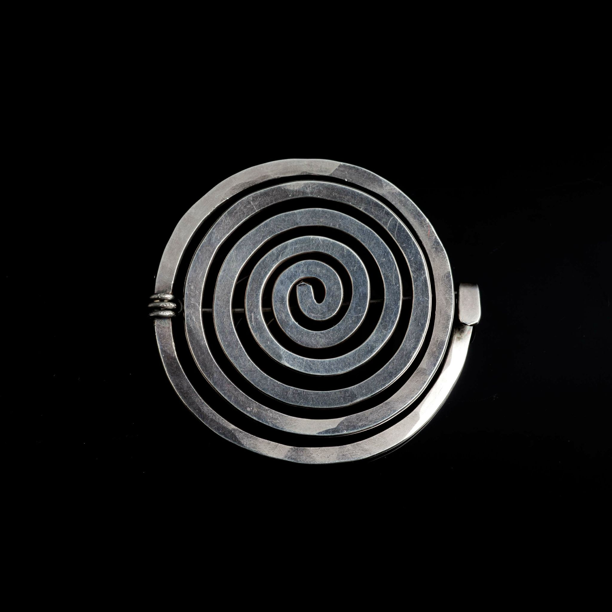 Alexander Calder, Silver Spiral brooch, c. 1932. Didier Ltd at Masterpiece London 2015. Unique sterling silver brooch in the form of a spiral with a steel fastening prong.
