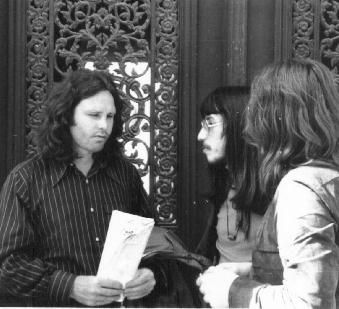 Jim Morrison in front of Hervé Mullers door, talking to Muller and Henri-Jean Henu, a journalist.
