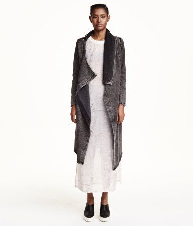 Long sweatshirt cardigan with a collar and wrap-style front. Concealed buttons at top, side pockets, and raw edges at cuffs and hem.