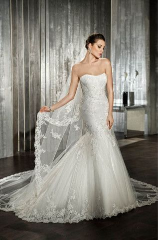 Gorgeous fitted Demetrios Wedding dress with lace applique detailing throughout the gown. Flattering with it's strapless neckline & fit & flare shape, this dress is classic & modern. Dress size 16. Co