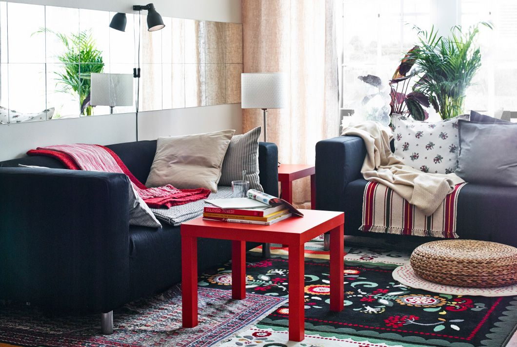 Living room with IKEA sofas, side tables and rugs layered