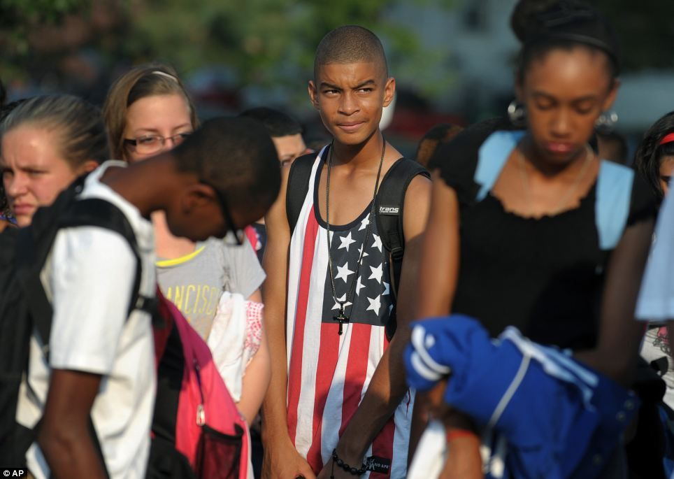 Eighth-grader Jancarlos Brito, 14, watches a Patriot Day ceremony with fellow students on Wednesday, Sept. 11, 2013 outside Northeast Middle...