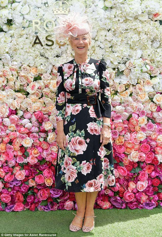 Blooming lovely!Dame Helen Mirren, 72 looked sensational for the sporting event based in Berkshire as she posed for pictures in front of a floral wall inside the racecourse