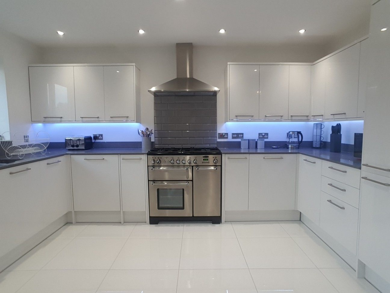 White High Gloss Kitchen With Range Oven Grey Mirror Chip Quartz Worktops And High Gloss Tiles F High Gloss Kitchen White Gloss Kitchen Gloss Kitchen Cabinets