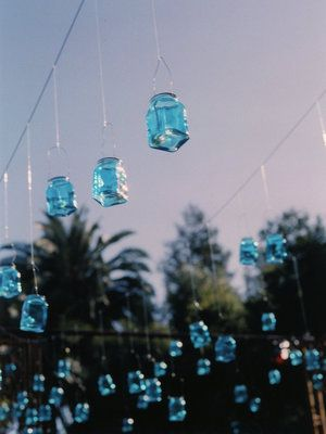 #Turquoise glass #lanterns containing LED lights hang from a Mexican-inspired wrought-iron #canopy over the dance floor. (Photo by Elizabeth Messina)