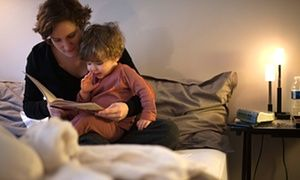A woman reads a story to her child. A recent survey found that a third of parents never read a bedtime story to their children.