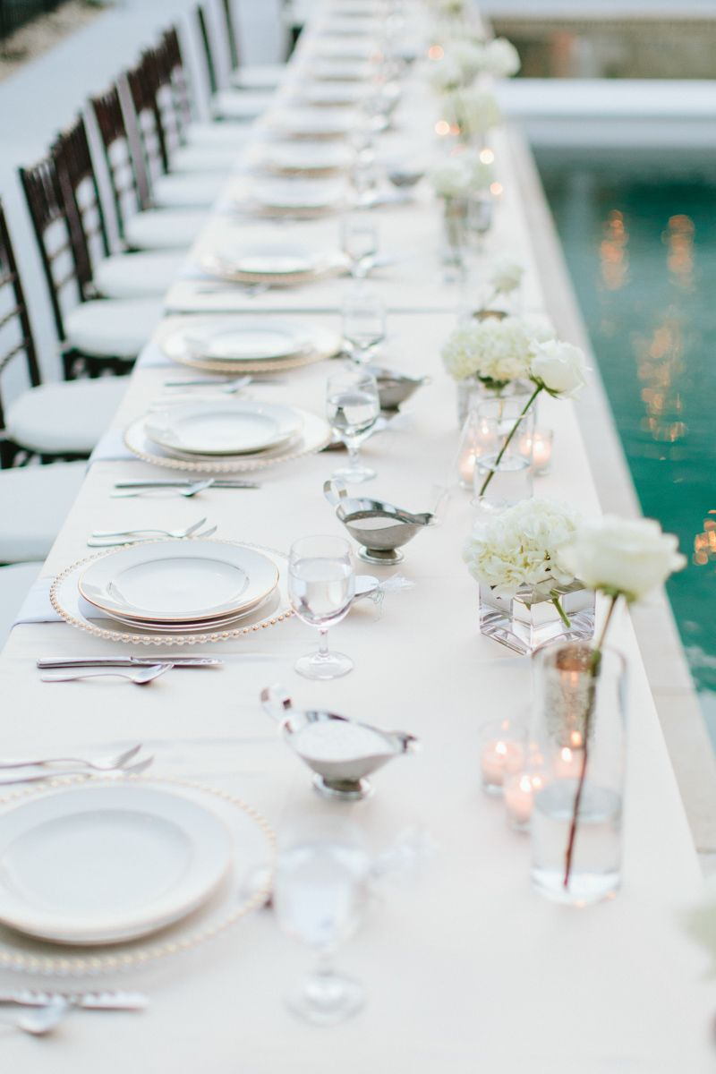 Simple and romantic centerpieces on rectangle tables around pool in ...
