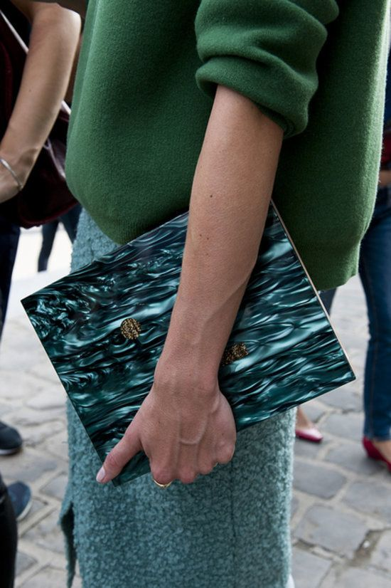 Perfect accessory placement: a moody clutch echoes the same hues in her skirt. #PFW #streetstyle
