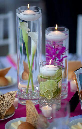 tall glass vases encased with cut flowers and cut limes this look is topped off using small floating votive candles which makes for a lovely summer