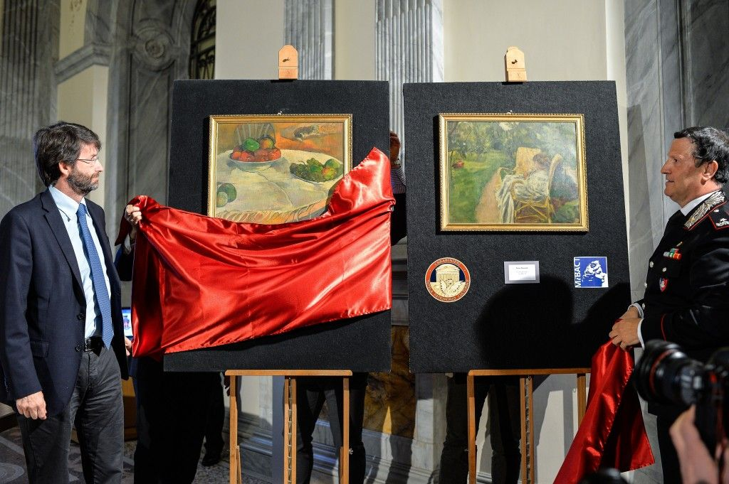The recovered Paul Gauguin and Pierre Bonnard paintings being unveiled by Italian officials. The current owner, a factory worker, hopes the artwork will be returned to him. Photo: Andreas Solaro, courtesy Agence France-Presse/Getty Images.