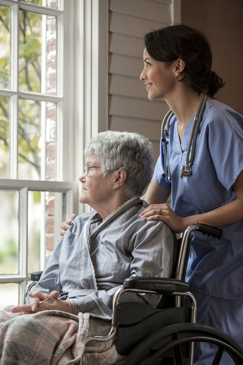 Photograph Nurse smiling with patient in wheelchair near window by Gable Denims on 500px
