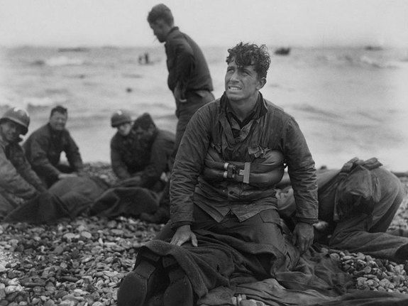 US Army soldiers recovering remains of comrades at Omaha Beach, Normandy, France, June 6, 1944.