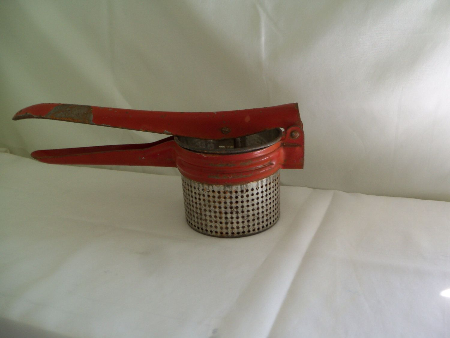 Vintage Burnt Orange Red Potato Ricer Smasher Masher Kitchen Decor Farmhouse Cooking Baking Tool. $16.00, via Etsy.