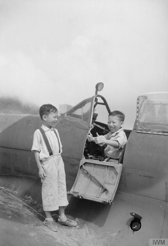 Two Chinese boys known as 'Big Wings' and 'Little Wings' who were adopted by 132 Squadron at Kaitak airfield, Kowloon, Hong Kong. Here 'Big Wings' shows his approval for the Spitfire by giving the 'thumbs up' sign.