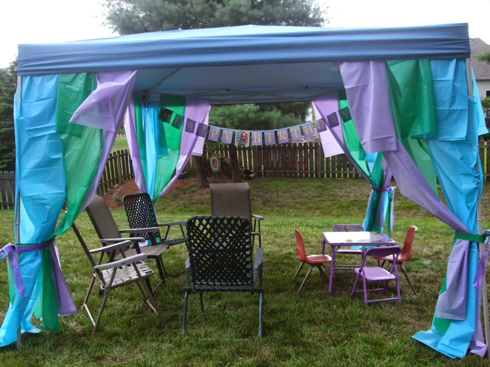 backyard pop-up tent decorated with strips of plastic tablecloths