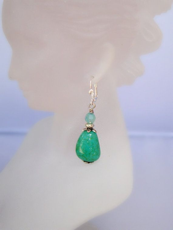 Beautiful turquoise bead earrings are surrounded by silver flower end caps and topped with a Swarovski sea opal crystal bead. Lever-back earring wires