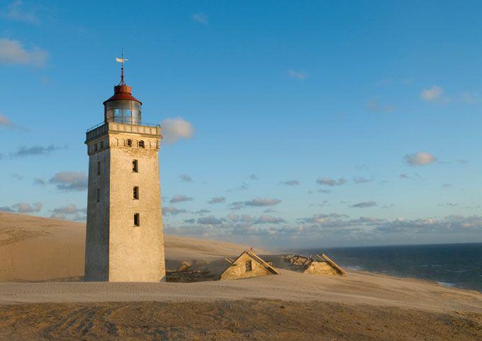Faro de Rubjerg Knude en Dinamarca. Curiosamente con el paso de los años se va enterrando más y más por las dunas de arena cercanas y se cree que en 15 años estará completamente cubierto. ¡ No te quedes sin verlo!