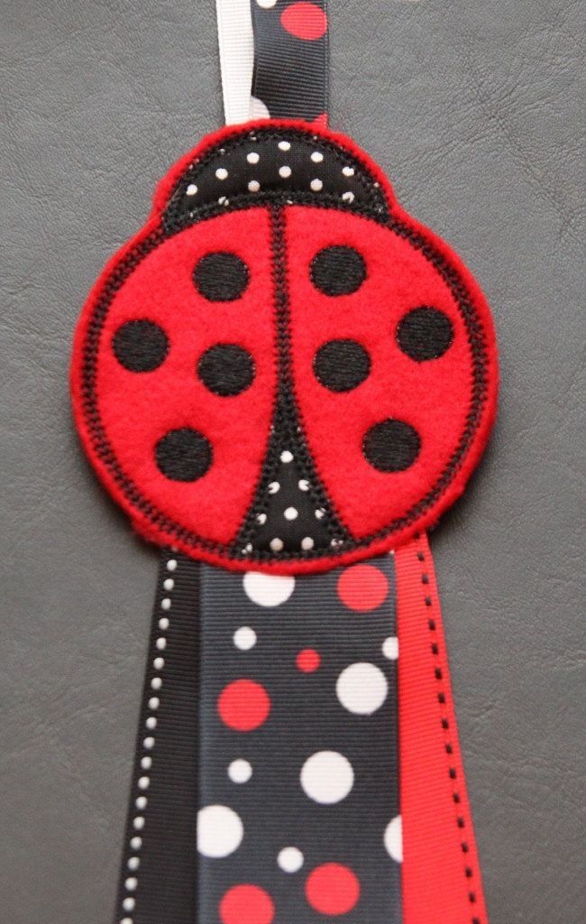 One machine embroidered ladybug felt stitchies barrette or hair clips keeper and holder. This organizer allows you to snap or clip all your favorite hair clips to the ribbon for a neat display!  http://www.etsy.com/listing/88245059/lady-bug-hair-clip-holder-keeper-felt