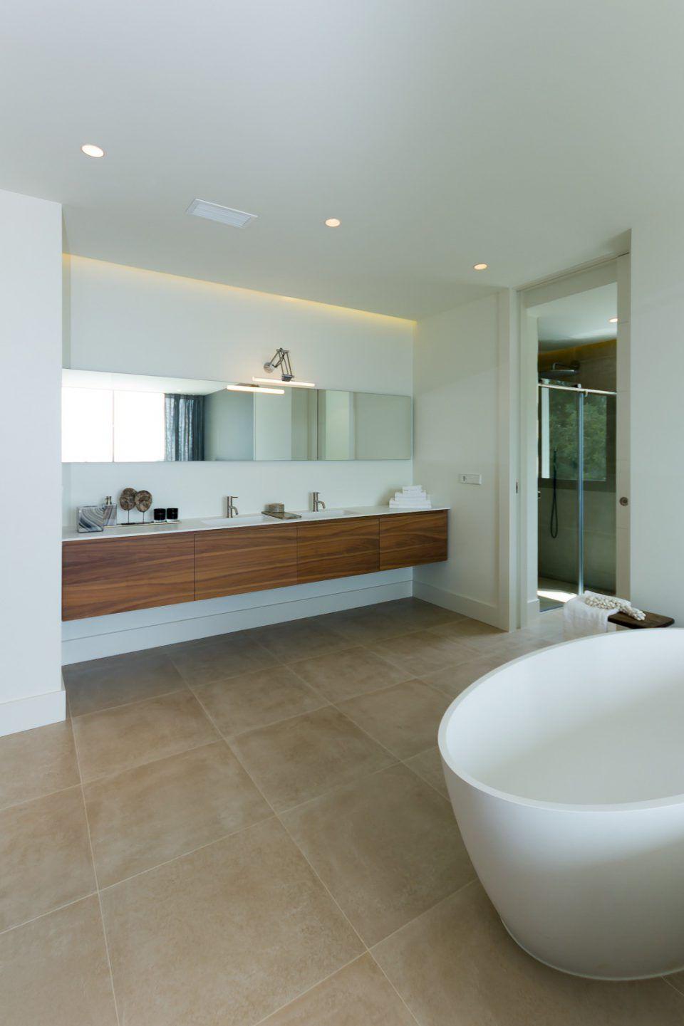 Badkamer inrichting met houten badkamermeubel en ronde badkuip ...