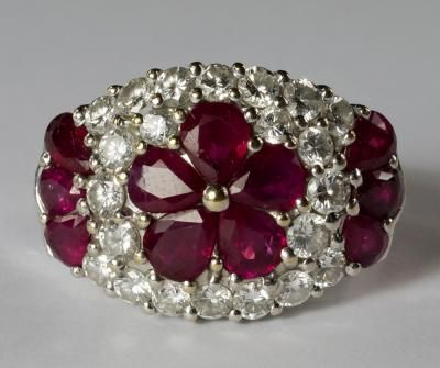 A striking 18ct white gold, diamond and ruby dress ring, with central floret of pear cut rubies, on a bed of round brilliant cut diamonds, with ruby petals to either side, approx 15cm wide, approx size P, approx 10.2g.